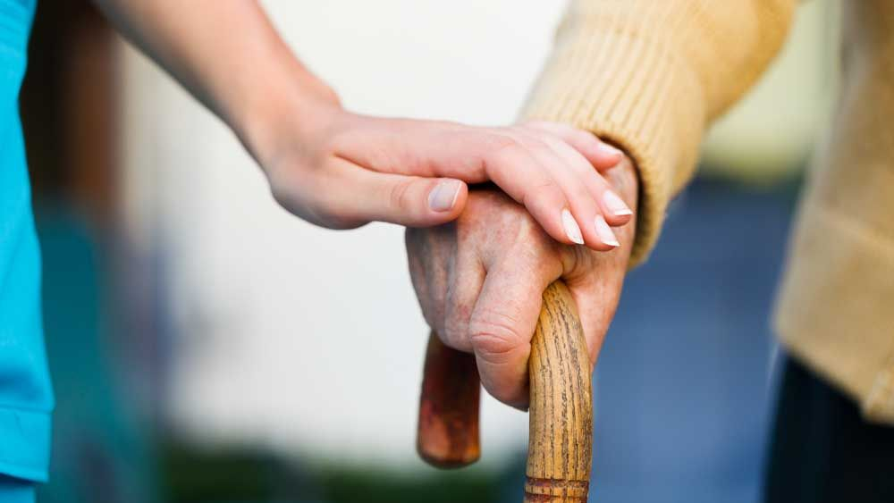 a carer holding an old mans hand