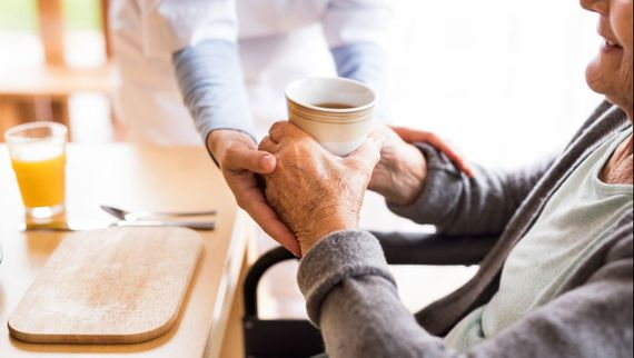 an old woman receiving a hot drink from a carer.